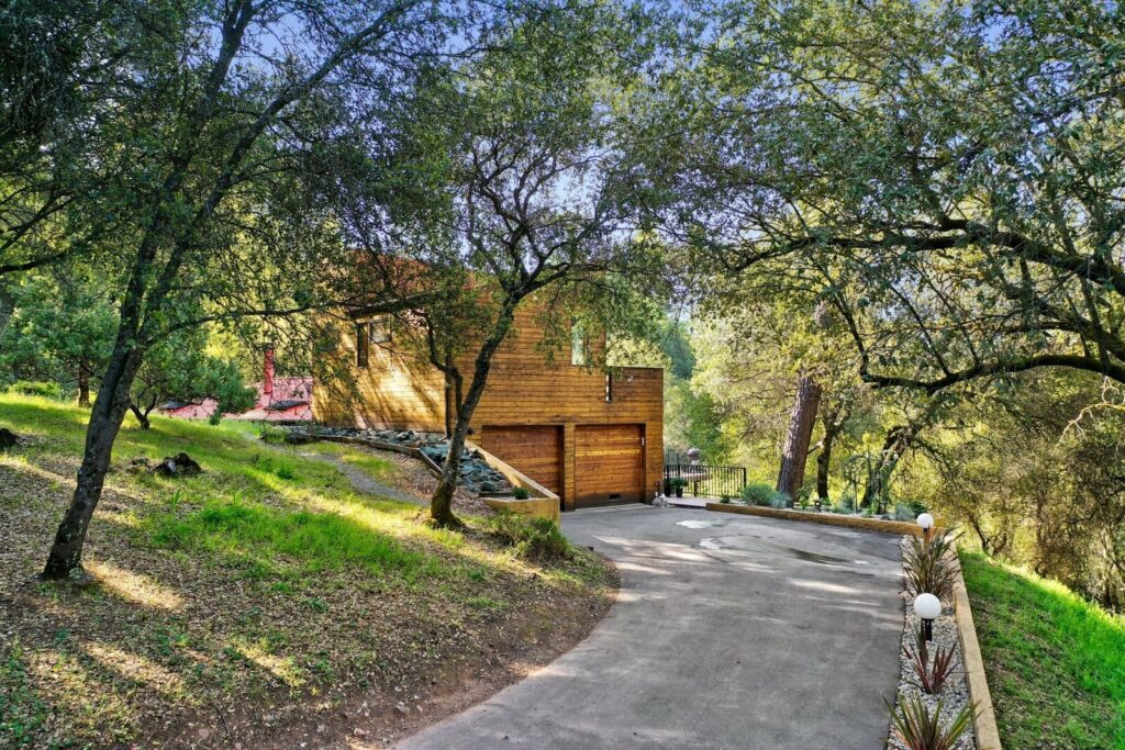 Clad in cedar, the Sunburst Residence is nestled on a three-acre lot with part of its north-facing facade built into the hillside. A paved driveway leads to the two-car garage.   Photo courtesy of Redfin.